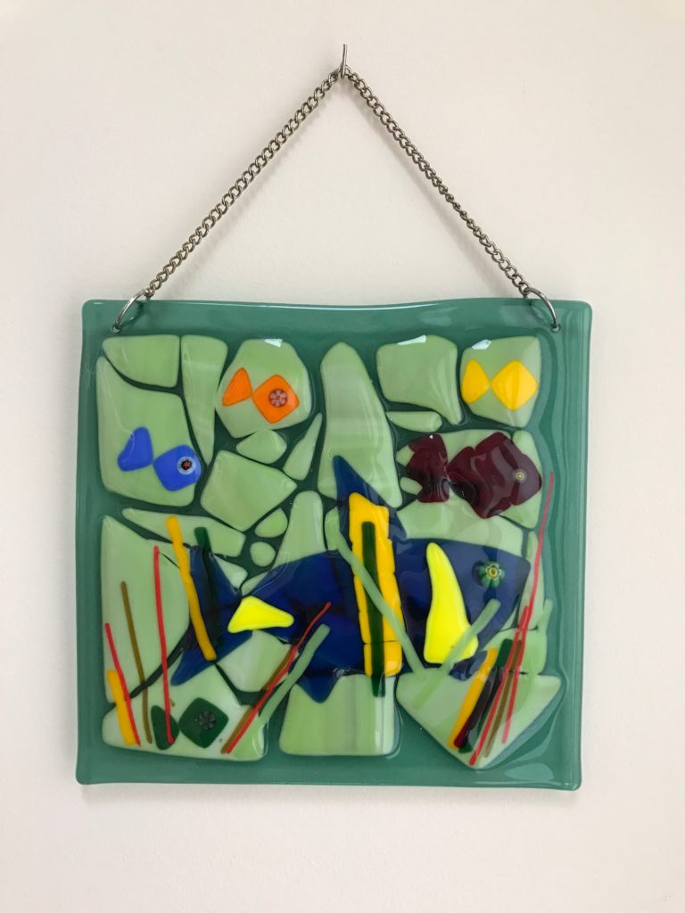 An underwater fish scene wall hanging created using cut glass that is fused together.